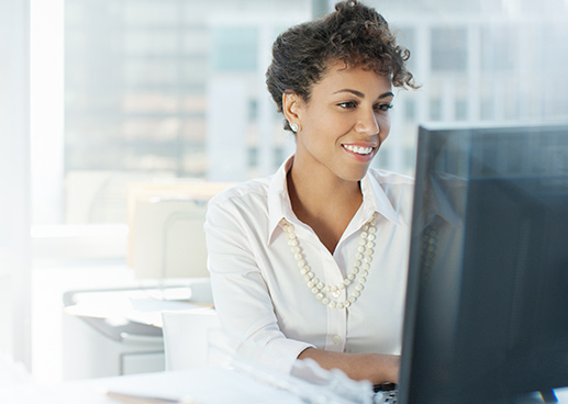 woman smiling and working on her desktop